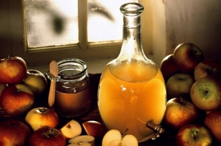 Apple vinegar in bottle, a jar of honey fresh apples